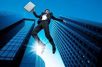 ビルの谷間でジャンプするビジネスマン