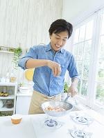 フライパンで料理をする日本人男性