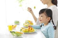 お母さんと一緒に食事をする女の子