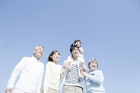 青空の下に立つ日本人の三世代家族