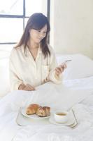 寝室で携帯を見ながら朝食を食べる日本人女性