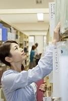図書室で本を探す大学生