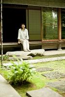 縁側に座り庭を眺める日本人女性