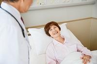 病室で医者の診察を受けるシニア女性
