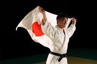日の丸をかざす男子柔道選手