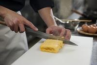 だし巻き玉子を包丁で切る調理師