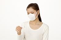 マスクをして体温計を見る女性