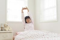 ベッドでストレッチをする寝起きの女の子