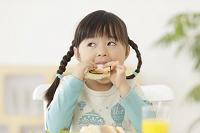 笑顔でサンドイッチを食べる女の子