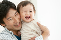 父親に抱っこされて笑う子供