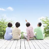 ウッドデッキに座る日本人男女達の後ろ姿