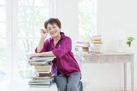 積み重ねた本にもたれて眼鏡を触る日本人のシニア女性