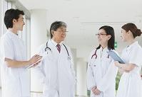 廊下で会話する笑顔の医療チーム