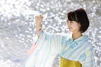 川の水面と風鈴を持つ浴衣の日本人女性