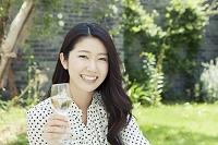 ワイングラスを持って微笑む20代日本人女性