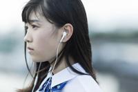 イヤホンで音楽を聴く日本人の女子学生