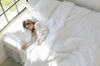 大きな窓のある広い寝室で眠る日本人女性