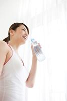 ペットボトルを持っている笑顔の日本人女性