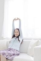 ソファで背伸びをする日本人女性