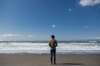 砂浜に立つ日本人男性の後姿