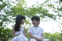 緑の中で見つめ合うハーフの男の子と女の子