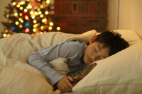 クリスマスツリーのある寝室で眠る日本人の男の子