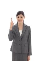 指を差すスーツの若い日本人女性