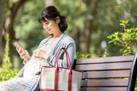 公園のベンチでスマートフォンを見る妊婦の日本人女性