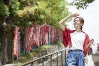 初夏の日差しを気にする日本人女性旅行者
