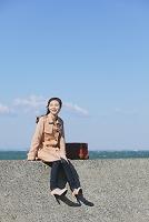 防波堤に座る女性