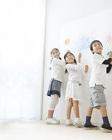 壁に絵を描く日本人の子供達