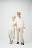 ステッキを持って寄り添う老夫婦