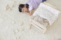 ぬいぐるみをおもちゃのベッドに寝かせてお昼寝する女の子