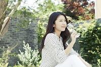 緑のある庭でワインを飲む20代日本人女性