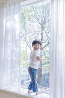 窓辺で振り返る日本人の男の子
