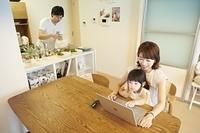 ノートパソコンを見る娘と母親