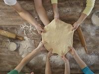 パン生地を伸ばす4人の手元