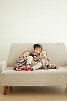 ソファーに座る男の子と双子の赤ちゃん