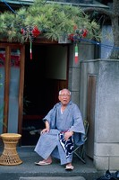 玄関先に座るシニア男性