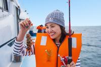 釣れたカサゴを持つ20代日本人女性