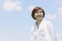 空と笑顔のシニア日本人女性