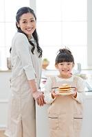 ホットケーキを持つ女の子と母親
