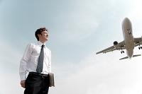 飛行機を背に佇むビジネスマン