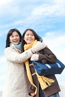 冬服を着て抱き合う女子中高生と母親