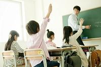 授業中に手を挙げる小学生