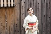板壁の前に立つ着物の日本の女性