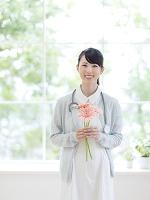 ガーベラの花を持つ看護師