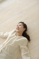 フローリングの床に寝転ぶ若い女性