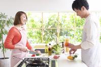 キッチンで料理する20代夫婦