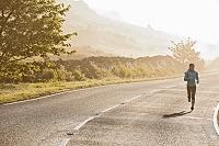 朝の道路を走るランナー